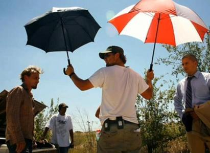 One of the crew holding parasols for Rob and Wentworth