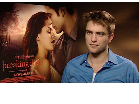 Rob Pattinson with the Breaking Dawn part 1 poster behind him.