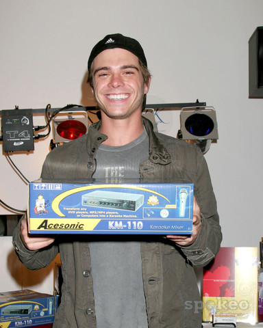 Matthew handing a karaoke box with a big smile on his face. :)