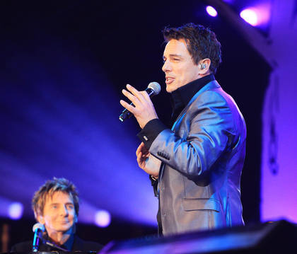 John Barrowman with his...VOICE!Thats his instrument :P Theres also a piano behind him..