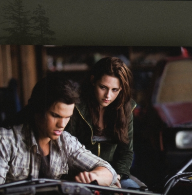 Taylor Lautner(as Jacob) in a scene from New Moon fixing a motorcycle,as Bella(played by Kristen Stewart) looks on.