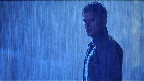 """Jensen in a scene from """"Smallville"""", standing in the pouring rain"""