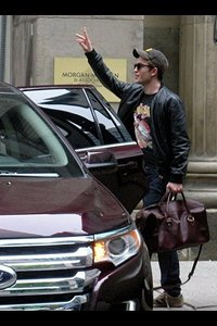 my baby with his arm raised as he waves to some fans<3