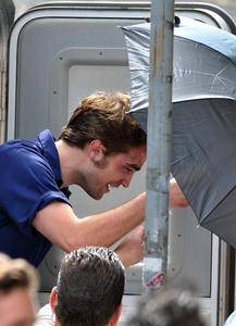 my baby in NY filming Remember Me,with an umbrella.Stay dry,baby<3
