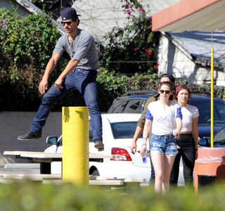 Taylor Lautner jumping over something,with his Twilight co-star Kristen Stewart looking on.<3