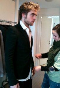 my hottie getting his wardrobe fitted,with a rack of clothes just behind him<3