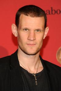 Matt Smith with a, looks like silver, necklace. And his new haircut.