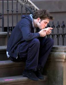 my handsome,smoking hot baby on the set of Remember Me in between takes sitting on the steps while smoking a cigarette<3