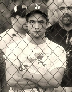 my handsome Robert standing behind a chain link fence<3