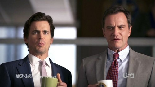 Matt holding a mug of coffee in his hand (a scene from White Collar)