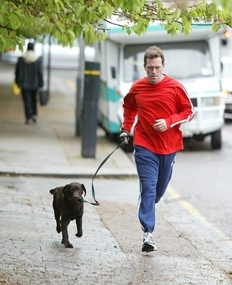 Hugh Laurie wearing a red 셔츠 while running with his dog Standley