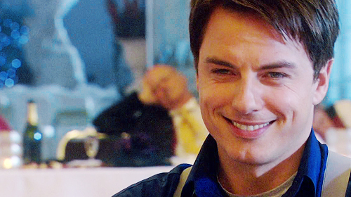 Brown Hair Blue Eyes Captain Jack Harkness hair Wearing a long manteau Brown Boots Being over 6ft Having a vortex manipulator Having a cheeky smile *COUGH* Jack Harkness *Cough*