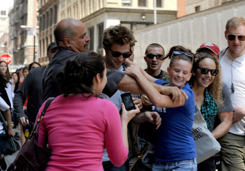 my handsome Robert getting lots of attention as he walks the streets of NY where he was filming Remember Me.That girl in the blue camisa is a little too close for comfort.Good thing Robert has bodyguards to guard that sexy body of his<3