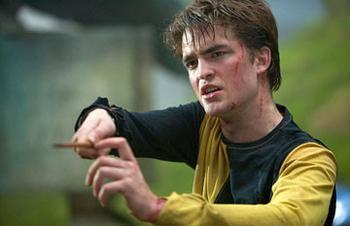 my gorgeous Robert in a scene from Harry Potter/GOF pointing a wand at the camera<3