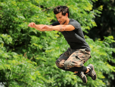 Twilight hottie Taylor Lautner with his arms out as he films a scene from Tracers<3