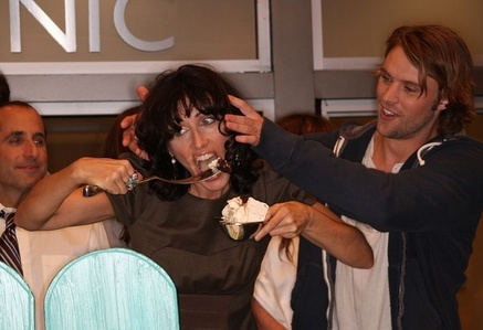 Lisa Edelstein eating cake to celebrate the 100th episode of House MD.