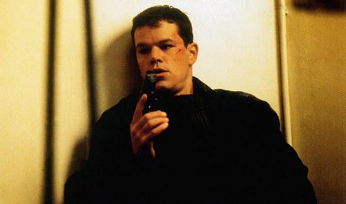 Holding a black gun.