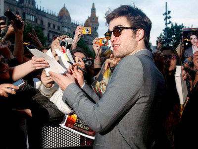 my baby with a pen in his hands as he signs autographs for some fans<3