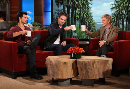 Robert and Taylor both holding cups on the Ellen show<3