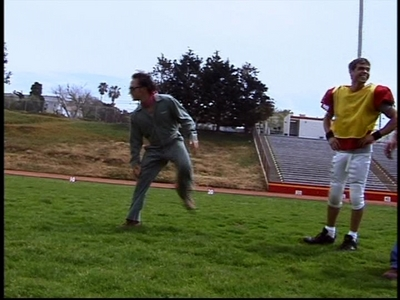 Matthew in yellow and red watching Rob Schneider who's about to kick a football to the goal. :)