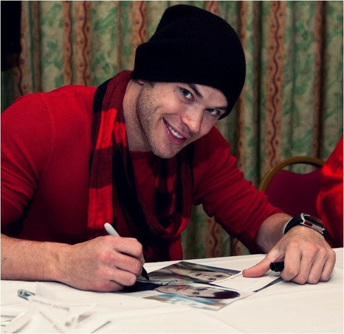 Kellan in a red sweater and red checkered scarf<3