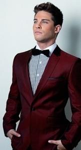 Dean Geyer wearing a red suit