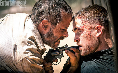 my handsome Robert being threatened par Guy Pearce in a still from their movie,The Rover.How dare he threaten my baby!!!!!!!!!