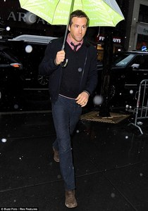 Ryan Reynolds walking in the rain with an umbrella