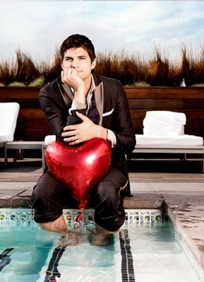 Ashton Kutcher sitting at the edge of a pool