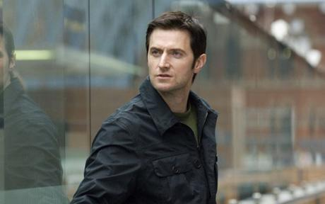 Richard Armitage with a Wand of windows behind <3