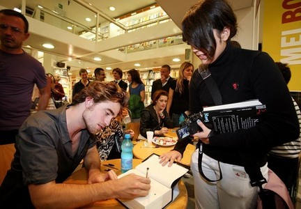 my sweetie signing his autograph in the Breaking Dawn book<3