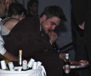 Robert eating some wings at the Eclipse after premiere party...looks yummy(and I don't mean the wings)<3