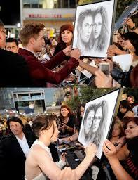 Robert and Kristen at the Eclipse premiere signing a framed picture of them<3