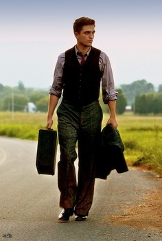 Robert carrying a suitcase in one hand and a جیکٹ in the other<3