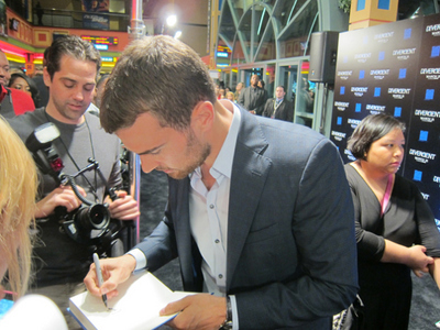 Theo looking down as he signs something for a fan<3
