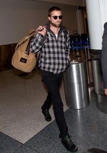 Robert carrying a bag as he walks through the airport<3