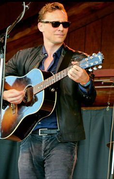 Tom Hiddleston with a guitar<3