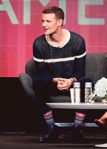 Matt Smith wearing colorful socks<3