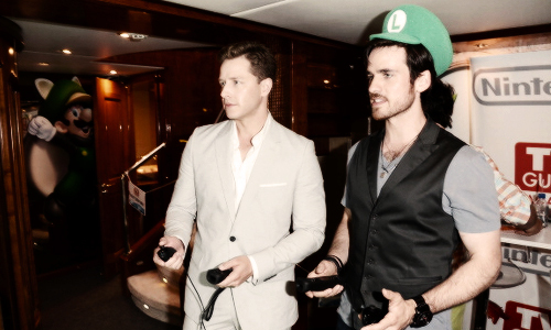 Colin O'Donoghue wearing a Luigi hat while he plays a video game xD