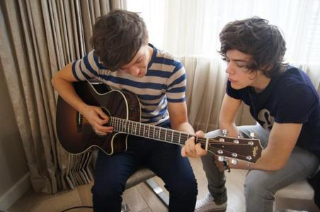 One Direction's Louis Tomlinson holding a guitar, watched on द्वारा Harry Styles.