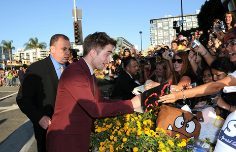 my gorgeous babe,Rob,signing a fan's copy of the Eclipse book at the Eclipse premiere<3