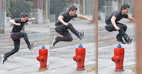 Taylor jumping over a आग hydrant<3