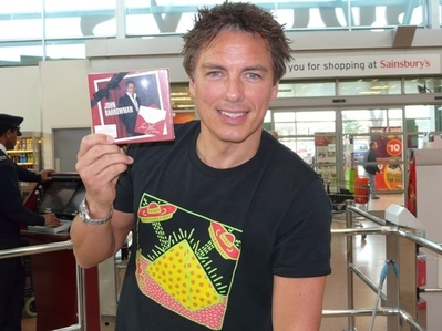 John holding a cd,which he's on the cover of<3