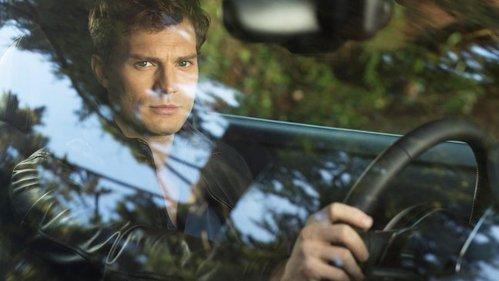 Jamie Dornan behind the wheel of a car<3