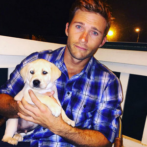 Scotty,the hotty in a plaid shirt,holding his newly adopted puppy<3