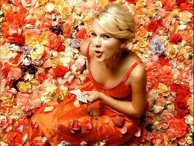 Taylor in an مالٹا, نارنگی dress