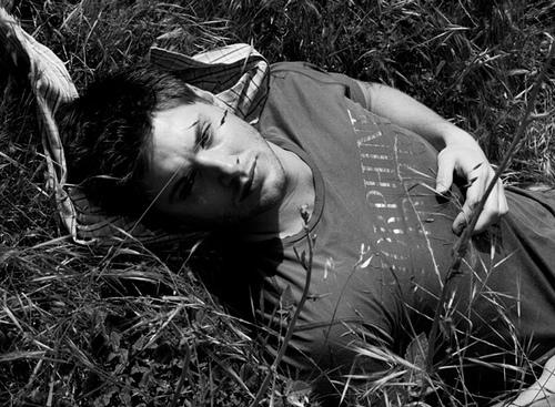 Jensen in b&w lying in the grass<3