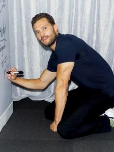 Jamie kneeling as he autographs a door