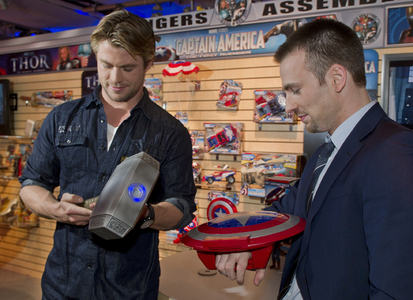 Chris Hemsworth and Chris Evans with smaller versions of their Avengers character's weapons
