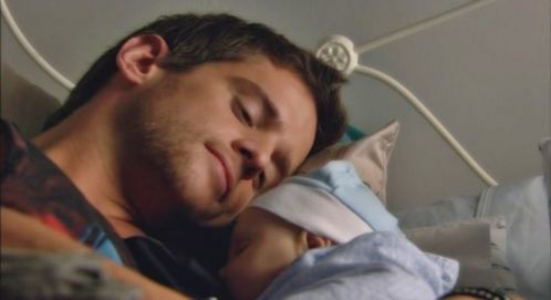 Post a picture of an actor lying with a baby.